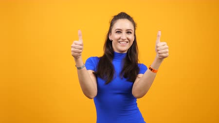 yelow : Cheerful positive and joyful woman showing thumbs up on orange yelow background. Pretty candid girl happinnes and lifestyle. Hand gesturing