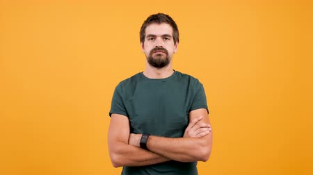 perspiration : Handsome man in casual t-shirt sweating from hot weather isolated on yellow orange background