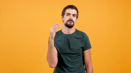 slapping : Attractive man slaps himself a couple of times on yellow orange background. Silly funny person