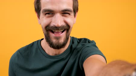 rozhovor : Adult bearded man vlogging with his camera on yellow orange background. Modern lifestyle
