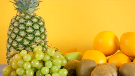 section : Healthy and organic exotic fruits on yellow background. Dolly footage revealing tasty and natural variety of fruits