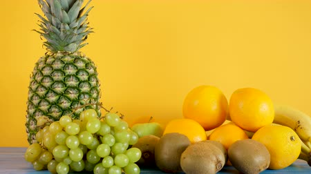 section : Zoom in footage on oranges, bananas, pineapple, kiwi and grapes on yellow background. Healthy and tasty nutrition. Summer diet