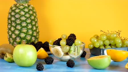 kivi : Delicious healthy home made fruit salad in glass bowl on yellow background. Parallax dolly footage