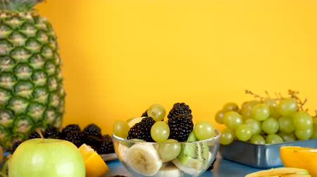 kivi : Exotic fruit salad made from bananas, kiwi, grapes and berries on yellow background. Zoom out dolly footage of tropical exotic nutrition Stok Video