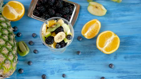питательный : Fresh healthy summer diet of fruit salad in plastic cup on vintage blue background. Top view dolly footage