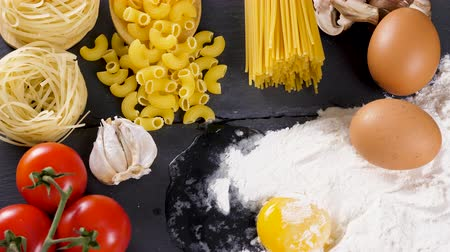 olasz konyha : Spaghetti, pasta and uncooked macaroni on dark table next to ingredients for dinner
