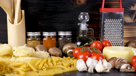 tomate cereja : Zoom out raw uncooked variety of pasta next to fresh vegetables on wooden board. Dolly slide footage Stock Footage