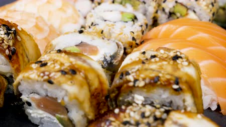 soy : Sushi rolls in variety mix on black stone plate. Dolly slide parallax type footage