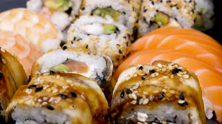 seafood dishes : Sushi rolls in variety mix on black stone plate. Dolly slide parallax type footage