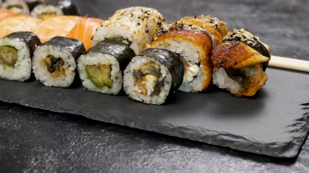 seafood dishes : Healthy, delicious and traditional sushi rolls on black stone plate. Dolly footage