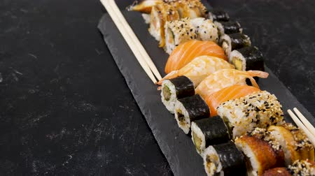 nori : Rolls of traditional sushi on black stone plate. Dolly slide parallax type footage