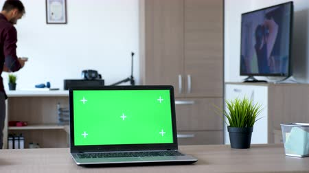 cihaz : Notebook with isolated green screen mock up in the middle of a living room. A man walks in the room while the TV is on and sits comfortably on the couch Stok Video
