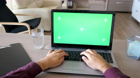 em branco : Businessman hands typing on laptop keyboard with a green screen chroma mock up on a desk in the living room of his house. Dolly slider 4K footage