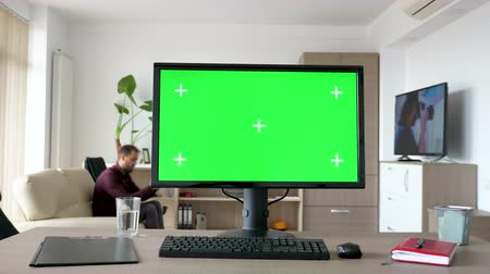 personal computers : Personal PC with big green screen chroma mock up on the table in the living room. A man walks in the background while the TV is on and sits on the couch looking at his smartphone Stock Footage