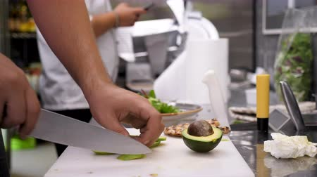 avocado : Cutting avocado in pieces on a cutting board in the kitchen