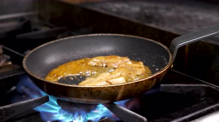 pasztet : Cook cooking foie gras on stove in kitchen. At the end he makes an open fire and the camera zooms out