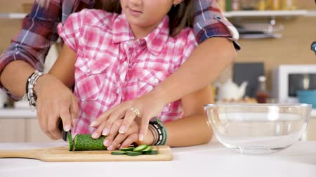 cuketa : Mother helping her young daugher to cut a cucumber on a cutting board in the kitchen Dostupné videozáznamy