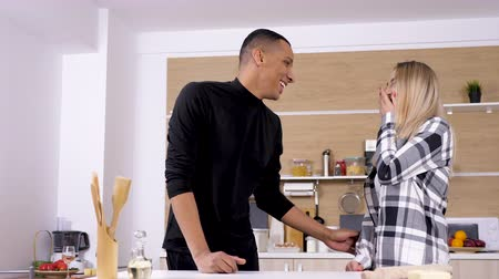 межрасовый : Beautiful young couple at the kitchen embracing each other and laugh. Interracial mixed couple made of afro american african man and caucasian blonde woman. Shot on cinematic camera in 4K UHD