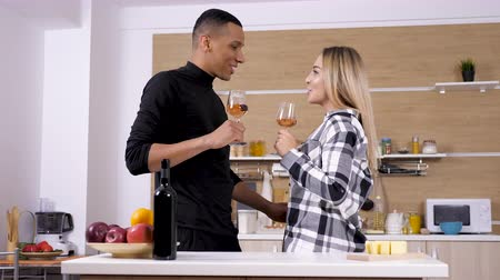 ırklararası : Gorgeous interracial couple drinking wine at the kitchen. They have a great fun time, smiling and laughing. She is a caucasian woman he is an afro american man. Shot on cinematic camera in slow motion 4K UHD Stok Video
