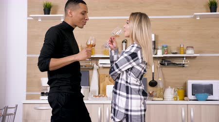 şarap kadehi : Happy mixed race ethnicity couple in the kitchen drinking wine and spending good time. Dolly slider 4K UHD footage Stok Video