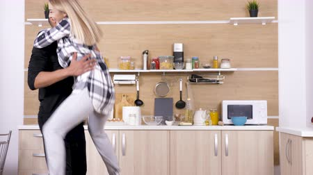 ırklararası : Blonde caucasian woman jumps in arms of afro american african man in the kitchen. Interracial couple. Dolly slider 4K footage Stok Video