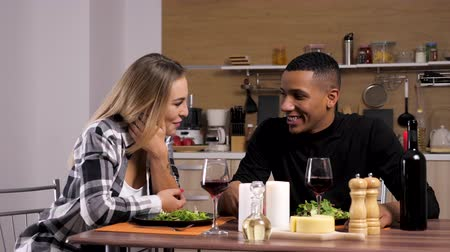 família : Interracial couple talking and smiling in the kitchen at candle light dinner. Beautiful blonde woman and african man. Slow motion 4K footage Vídeos