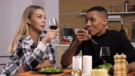 família : Interracial couple in the kitchen having dinner at candle lights, smiling, laughing and drinking wine. Dolly slider 4K footage
