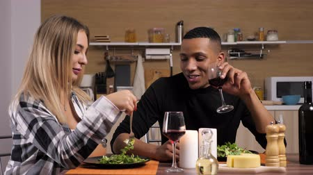 ırklararası : Gorgeous interracial couple dinning at candle lights in the kitchen. They smile, eat and drink wine. Dolly slider 4K footage