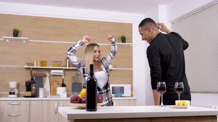 buta : Interracial couple dating at home, dancing and having fun in the kitchen. Dolly slider 4K footage