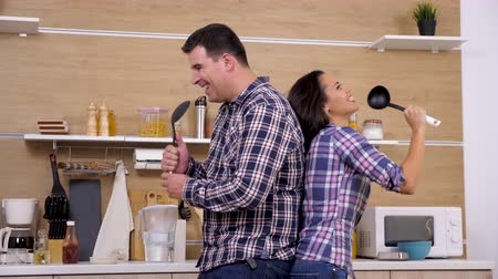 dinleme : Happy positive couple in the kitchen singing in big plastic spoon back to back. Slow motion 4K footage. Joyful and loving wife and husband