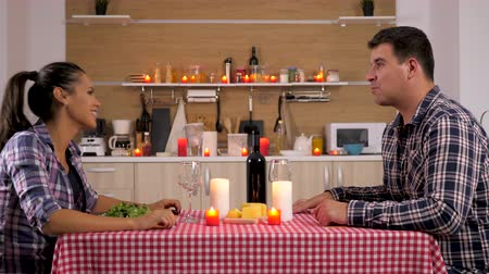 família : Man pouring wine to his girlfriend at candle light dinner in the kitchen. Dolly slider 4K footage