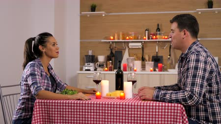 şarap kadehi : Pretty couple having candle light dinner in the kitchen. They drink wine, and eat cheese and salad. Dolly slider 4K footage