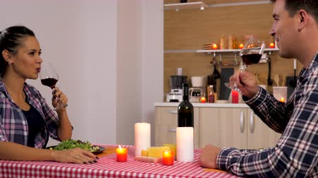 datas : Beautiful couple in the kitchen eating at candle lights. Dolly slider 4K footage Stock Footage