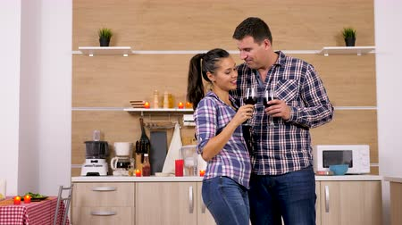 família : Couple in the kitchen with wine glasses in hands. They are having a good time.