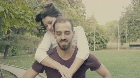 parte : Young girlfriend jumps in her boyfriend arms in the park. Slow motion 4K footage with cinematic color grading