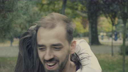 parte : Close up of woman jumping in her boyfriend arms in the park. Slow motion 4K footage with cinematic color grading