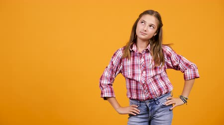 buta : Young girl making silly faces in front of the camera on yellow orange background. Isolated.