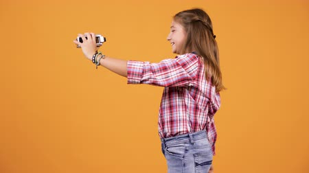 vlogging : Pretty young girl vlogging with a camcorder in hands over an yellow orange background