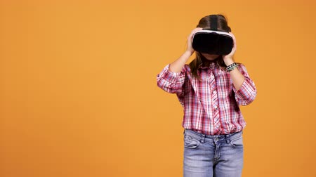 grãos : Young girl wearing a VR virtual reality headset on her head isolated over an yellow orange background in studio Stock Footage