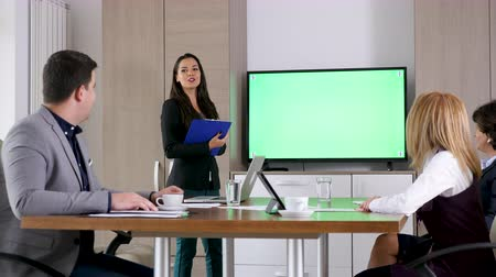 sala de reuniões : Beautiful businesswoman in front of green screen mock-up chroma TV with a clipboard in hands Stock Footage