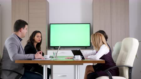 conference table : Business team in conference room looking at big green screen chroma mock-up TV than start talking to each other. Dolly slider 4K footage