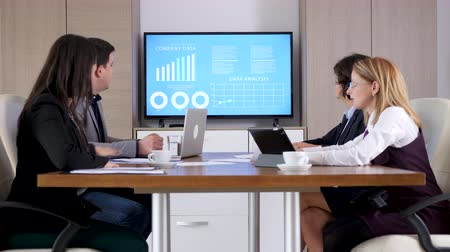 brifing : Business partners in the conference room talking to each other while a big screen TV in back projects animated chart and financial data Stok Video