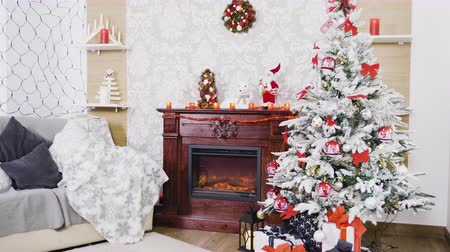 christmas tree with lights : Decorated Christmas Interior. There is a beautiful white christmas tree with gift boxes under it and a fireplace with toys and decorations on it. Stock Footage