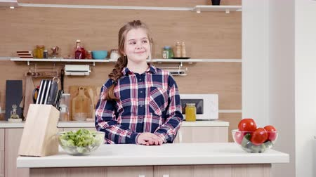 espectador : Positive teenager girl smiling to the camera. She walks in the middle of the kitchen and smiles to the viewer. Dolly slider slow motion 4K resolution footage Vídeos