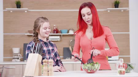 lunchen : Mother showing her daughter how to mix salad at the kitchen. They both have a great time. Dolly slider 4K resolution footage