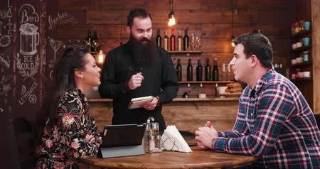 официант : Bearded waiter taking order from couple in vintage hipster restaurant pub Стоковые видеозаписи