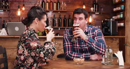 есть : Beautiful caucasian couple eating peanuts and drinking beer in rustic - vintage pub or restaurant. There is a bearded hipster bartender working at the counter in the background