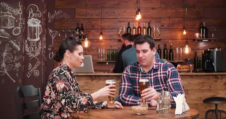 есть : Couple being served with a pizza in vintage pub or restaurant by a bearded hipster waiter. There is another person drinking at the counter.
