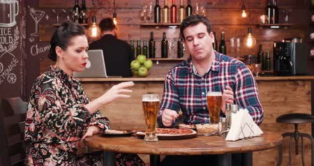 művek : Caucasian couple eating pizza and drinking beer in very cozy and stylish pub or restaurant. A bearded bartender is sitting in the background and works at the counter