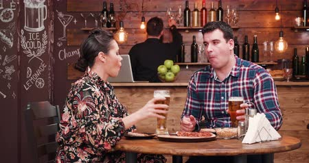 есть : Pizza and Beer is a stock footage presenting a beautiful couple in stylish pub or restaurant eating pizza and drinking beer. There is a bearded hipster bartender who sitts at the counter in the background